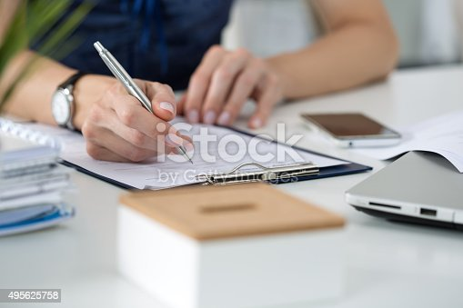 istock Woman writing something  sitting at her office 495625758
