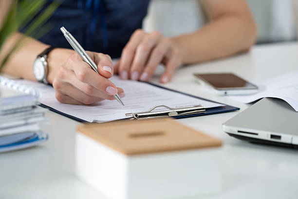 woman writing something  sitting at her office - form document stock pictures, royalty-free photos & images