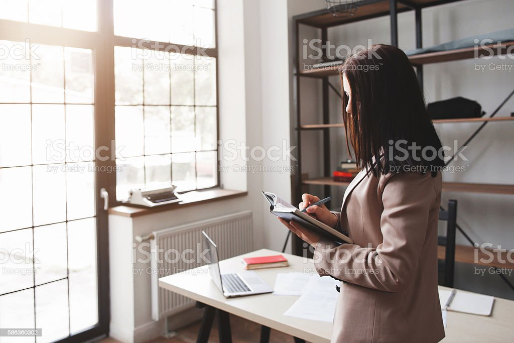 Woman writing 'to do list' in her notebook stock photo