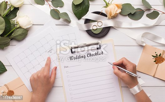 Woman writing wedding items in checklist for planning budget, panorama