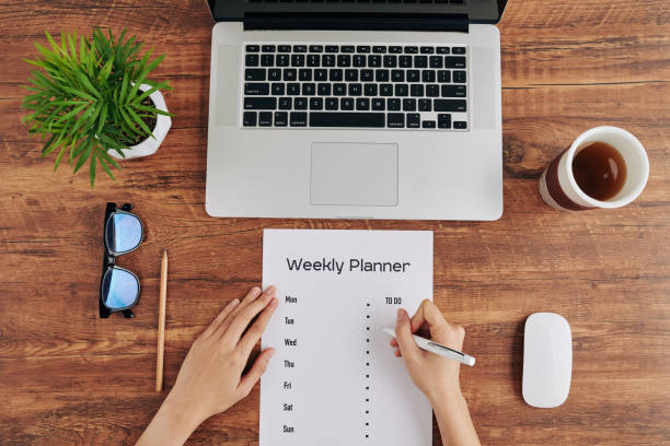Woman writing weekly planner stock photo