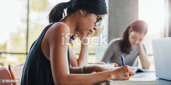 istock Woman writing with classmates studying in library 618548036