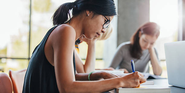 woman writing with classmates studying in library - jacob ammentorp lund stock pictures, royalty-free photos & images