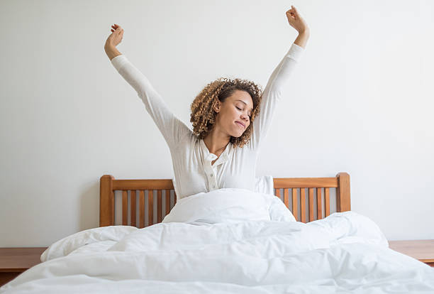 Woman yawning in bed stock photo