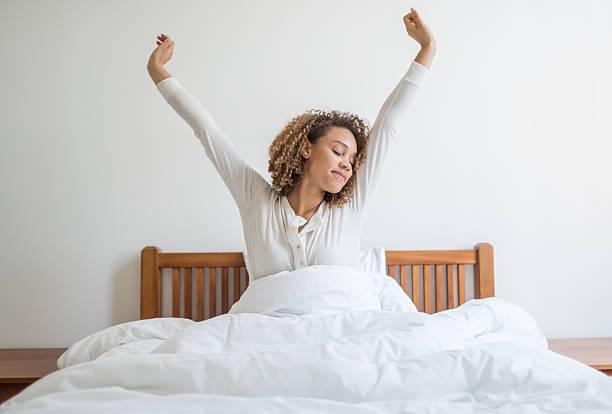 Mulher bocejando na cama - foto de acervo