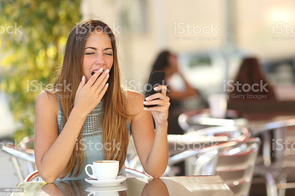 Woman yawning while is working at breakfast in a restaurant stock photo