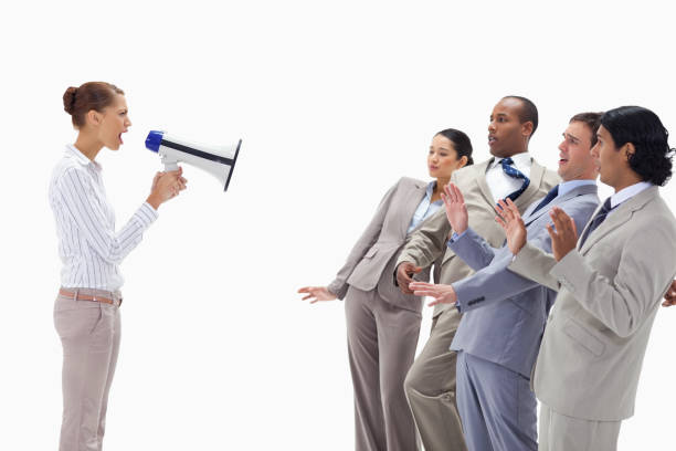 Woman yelling at business people through a megaphone stock photo