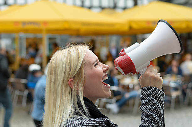 Woman yelling into a megaphone Woman yelling into a megaphone on an urban street voicing her displaeasure during a protest or demonstration, close up side view of her face activist stock pictures, royalty-free photos & images