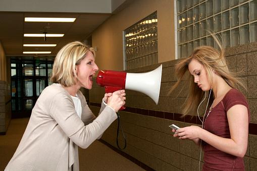 istock Woman yelling through a bullhorn at an unfazed teenage girl 172808685