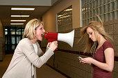 Woman yelling through a bullhorn at an unfazed teenage girl