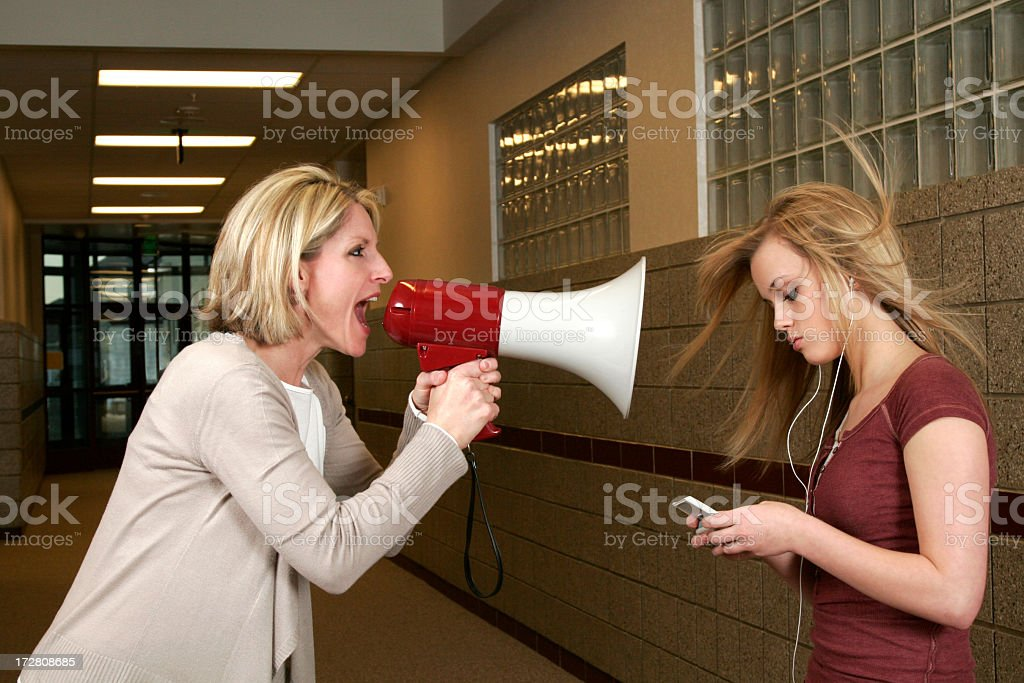 Woman yelling through a bullhorn at an unfazed teenage girl stock photo