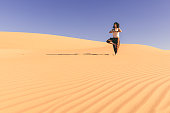 Yoga meditation on the sand dune,healthy female body in peace, woman sitting relaxed on sand, calm girl enjoying nature, active vacation lifestyle, Zen spa, wellness concept