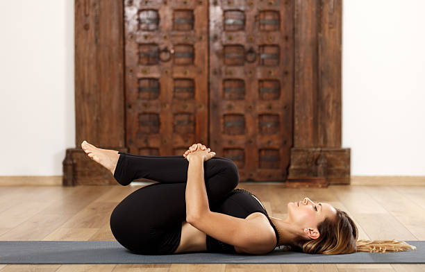 Woman yoga trainer in asana Woman yoga trainer in apanasana (knees to chest) pose apanasana stock pictures, royalty-free photos & images
