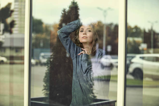 Woman young adult beautiful outside the window looking at the streets of the city through the glass stock photo