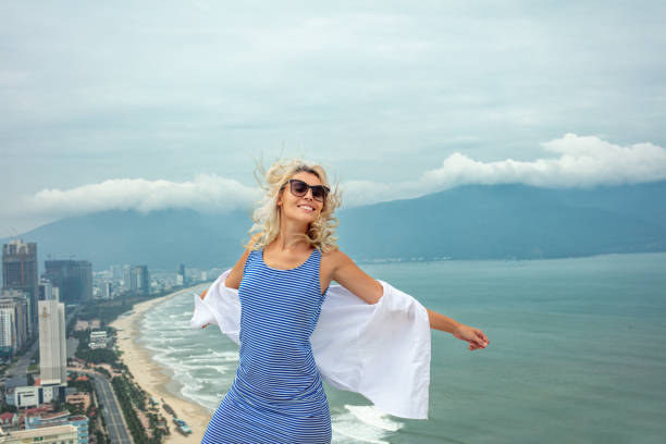 Woman young adult in a dress on the roof of a building with a view of the city's seascape on a Sunny day stock photo