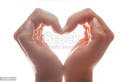 Woman's hands make a heart shape on white background, backlight. Love, emotions, happiness.