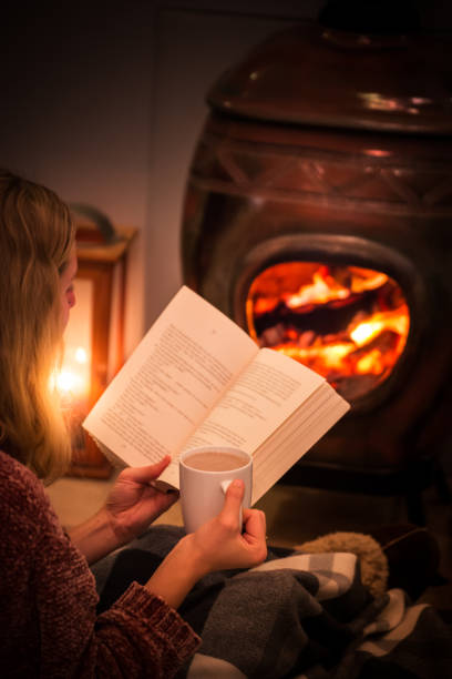Woman/girl sitting in front of a cozy fireplace during winter under a blanket  reading a book drinking coffee/hot chocolate. stock photo
