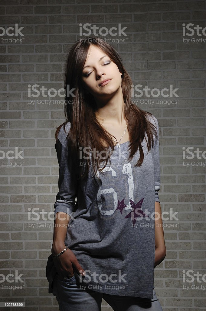 womanly brunette on brick wall background . stock photo