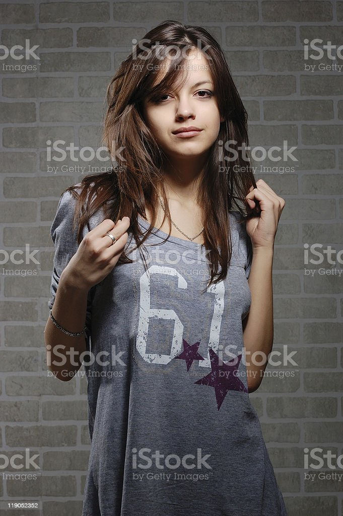 womanly brunette on brick wall background stock photo