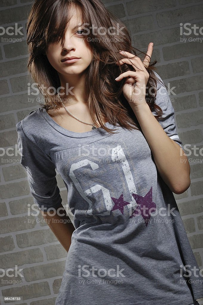 womanly brunette on brick wall background . royalty-free stock photo