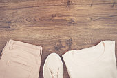 Womanly pink leather shoes, pants and sweater on rustic boards, copy space for text