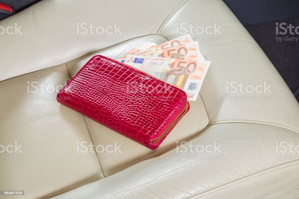 Womanly red wallet with euro money on the leather seat in the car interior. Car purchase, insurance and expenses. Money on fuel and repairs. Travel money. stock photo