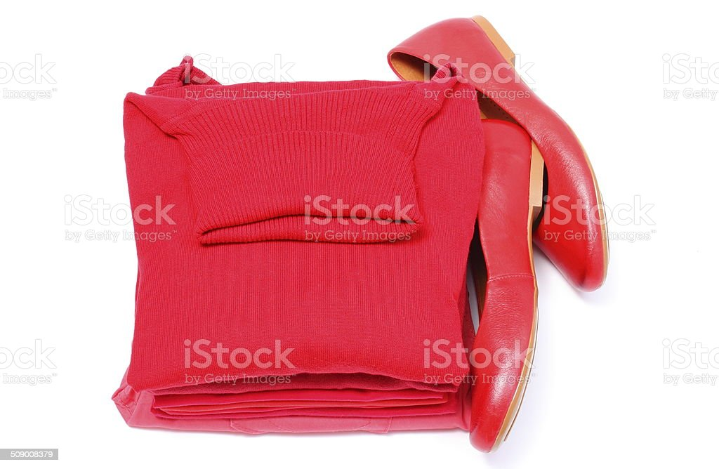 Womanly shoes and pile of red clothes. White background stock photo