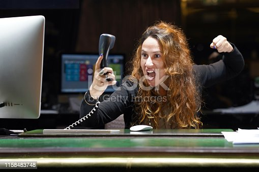 Woman-reception swears with the client of the hotel by phone. A woman is shouting into the phone's phone. Funny facial expressions, emotions, reaction of perception, stress, gilding, nerves.