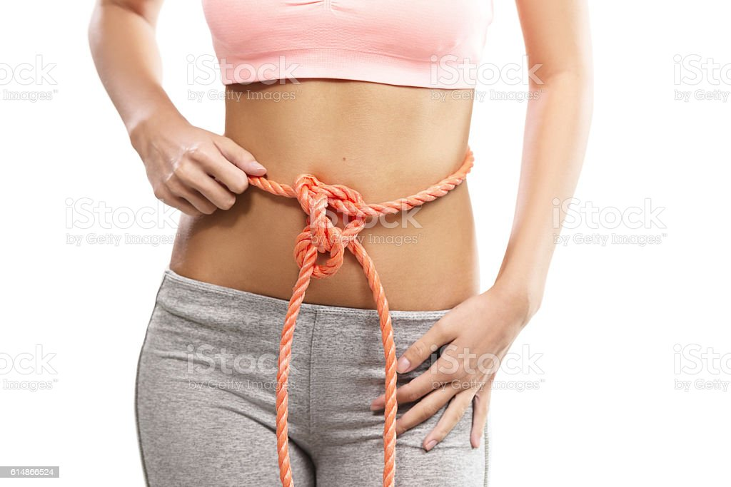 Woman's abdomen tied with a rope, conceptual stock photo