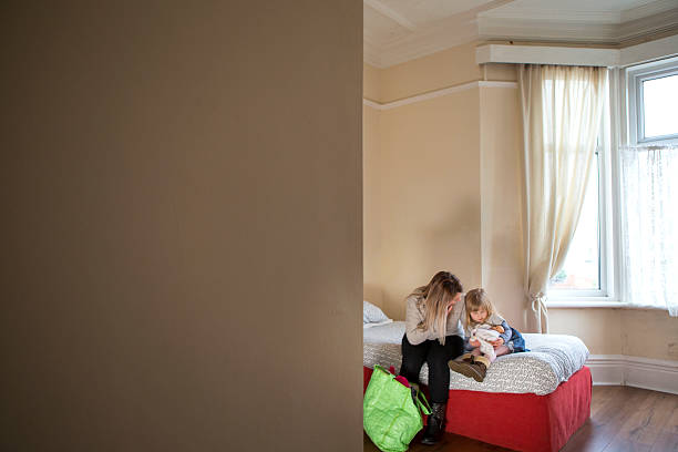 Woman's Aid A young mother and daughter sit on a bed in a dingy woman's support centre sheltering stock pictures, royalty-free photos & images