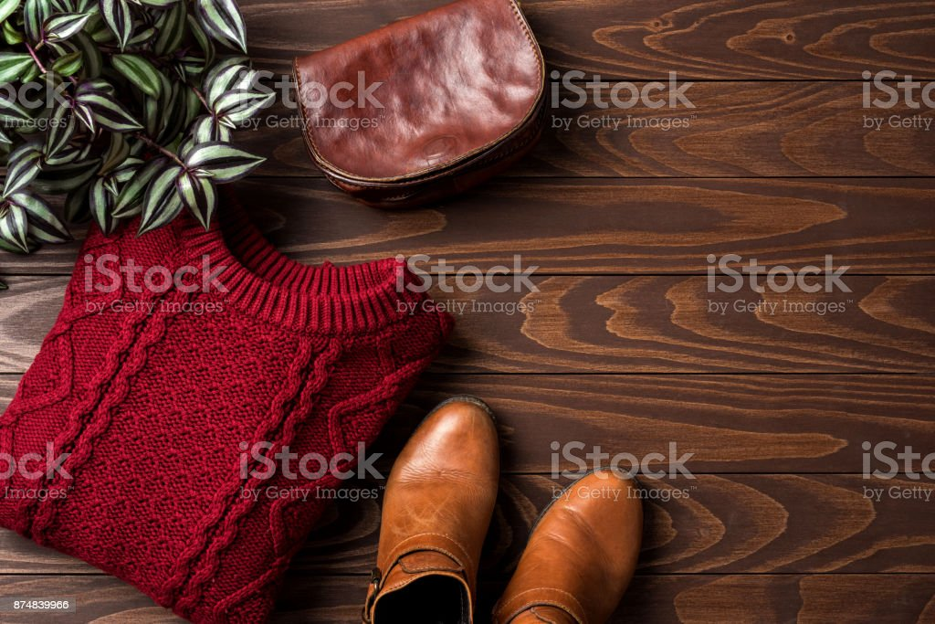 Woman's autumn or winter clothing over white wooden background stock photo