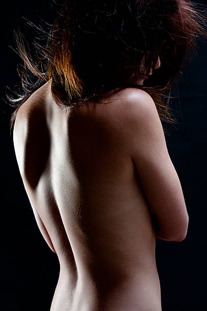 womans back cyoung womans back turned showing skin texture with low key lighting goosebumps stock pictures, royalty-free photos & images