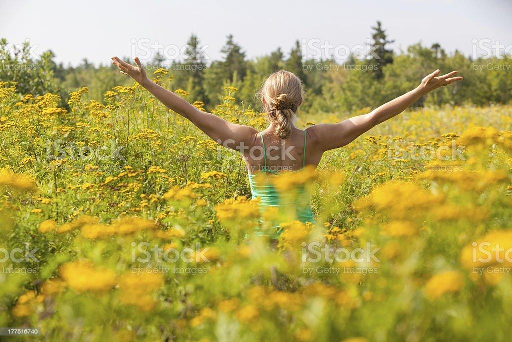 Kobieta praktykowania jogi na plecach w Łąka z żółte kwiaty – zdjęcie