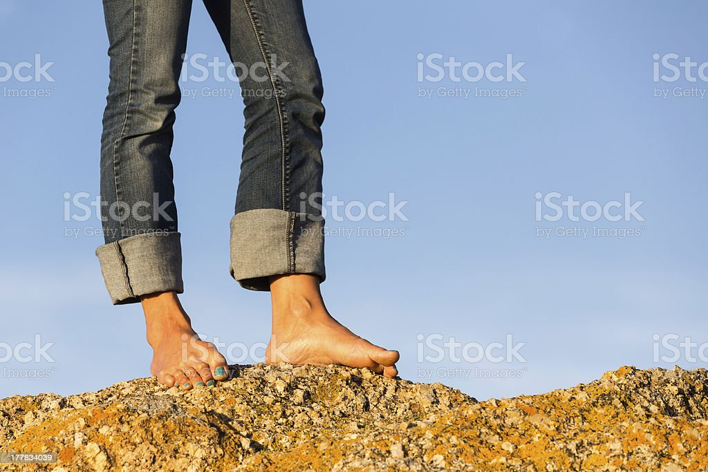 Woman's Bare Feet Standing on a Rock stock photo