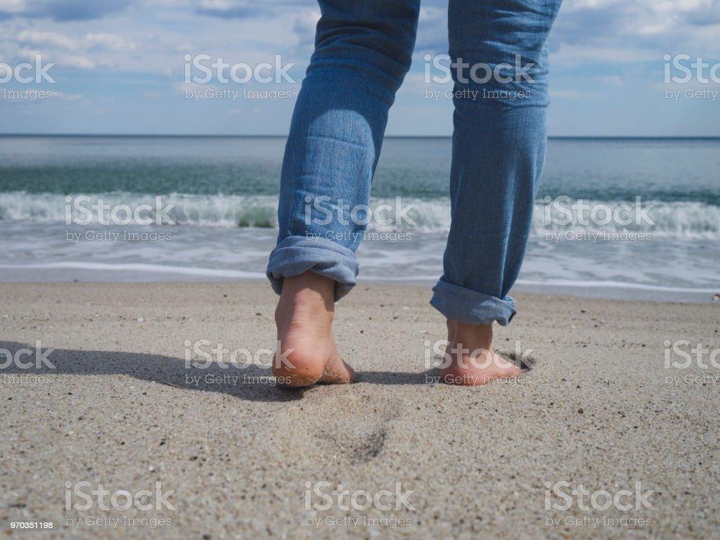 Woman's bare feet walking on a beautiful sandy beach towards the water stock photo