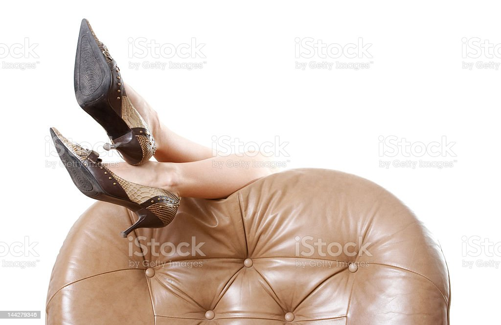 Woman's beautiful long legs laying on the armchair royalty-free stock photo