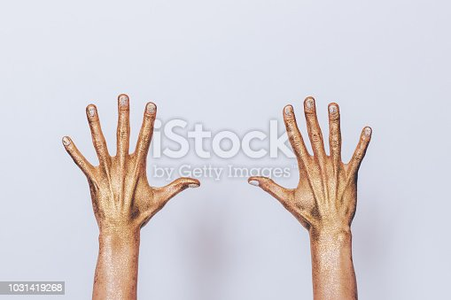 istock Woman's both hands painted golden sequins showing 1031419268