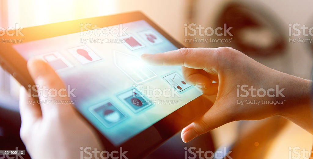 Womans controls Internet of Things in smart home with app Woman puts her finger on an icon of a house shown on the touch screen of a digital tablet. The tablet runs a smart home app. Concept of controlling wireless devices at home, also know as internet of things.  Accessibility Stock Photo