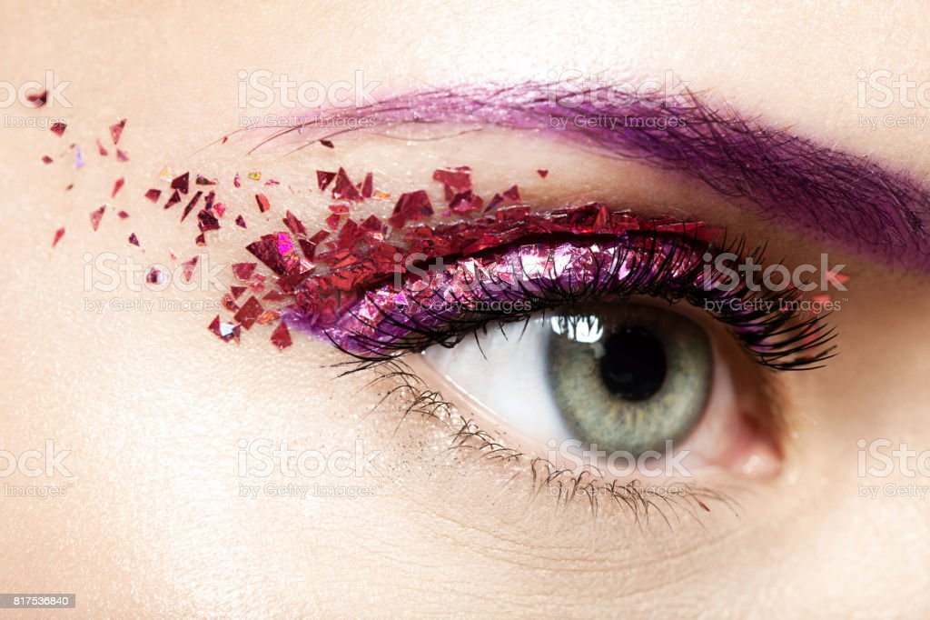 Woman's  eye with a shiny trendy makeup in violet tones with sparkles stock photo