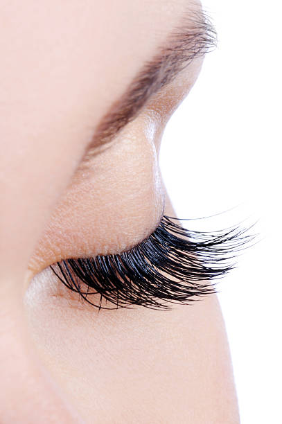 Woman's eye with long, dark false eyelashes stock photo