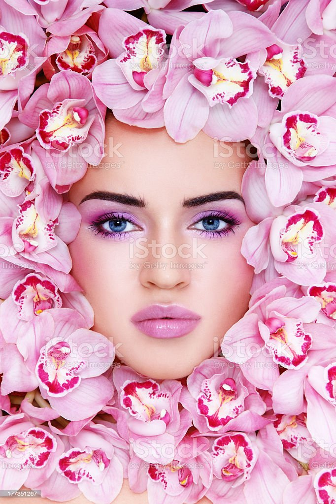 A woman's face surrounded by pink orchids royalty-free stock photo
