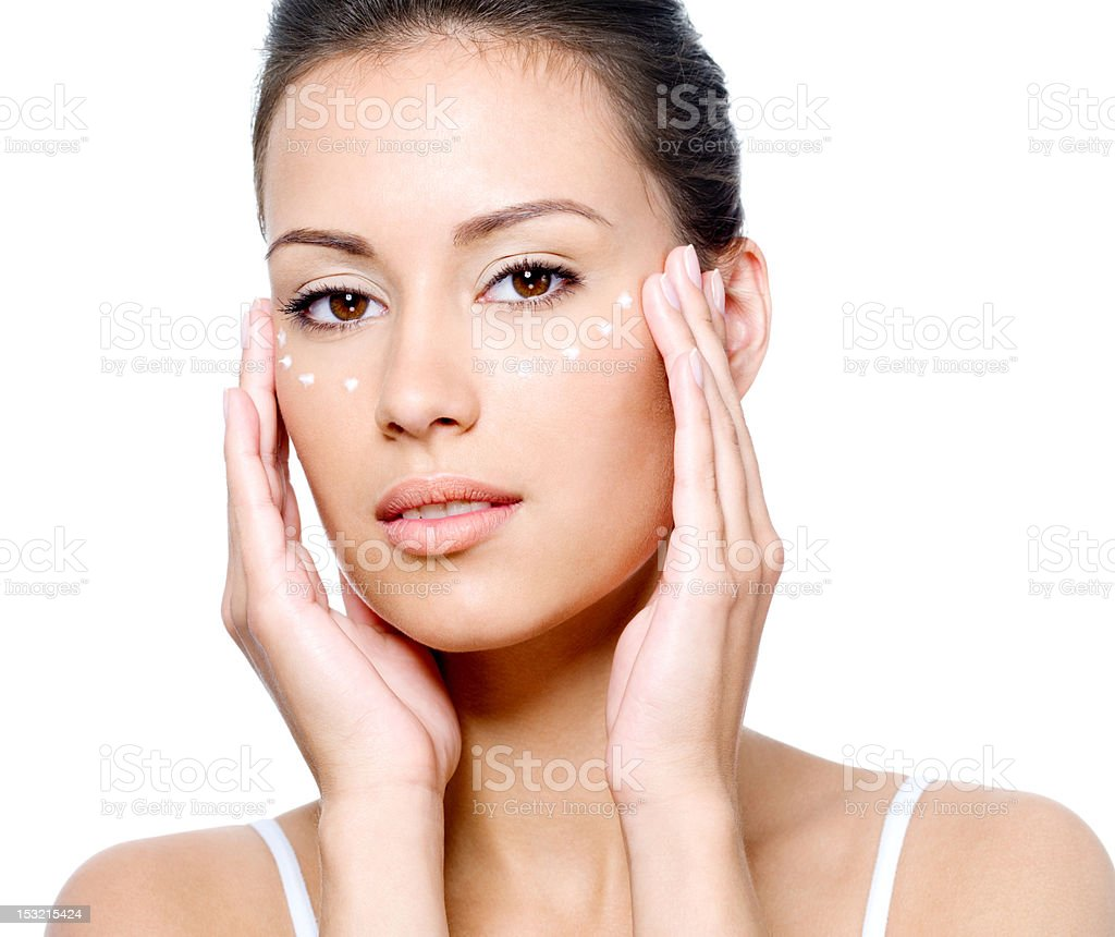 Woman's face with cream under the eyes stock photo