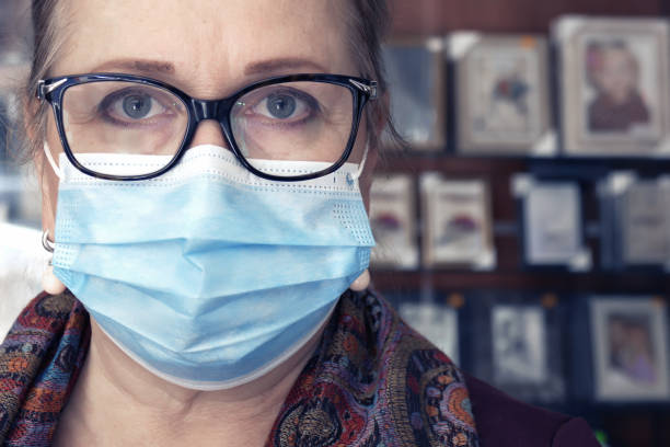 Woman's face with glasses and protective mask stock photo