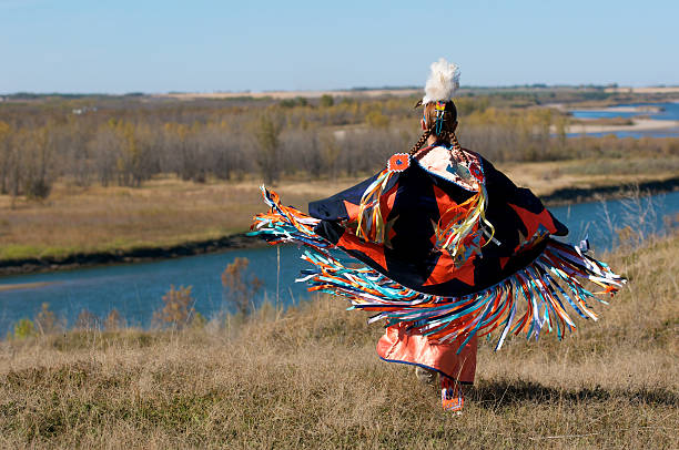 Woman's Fancy Shawl Dancer A woman performing a First Nations fancy shawl dance in a field alongside the river in Saskatoon, Saskatchewan indigenous peoples of the americas stock pictures, royalty-free photos & images