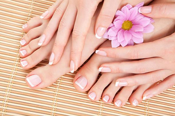 Weibliche Füße und Hände mit rosa Blumenmuster – Foto