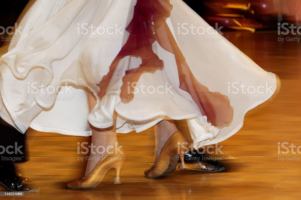 Woman's feet between man's dancing on parquet floor stock photo