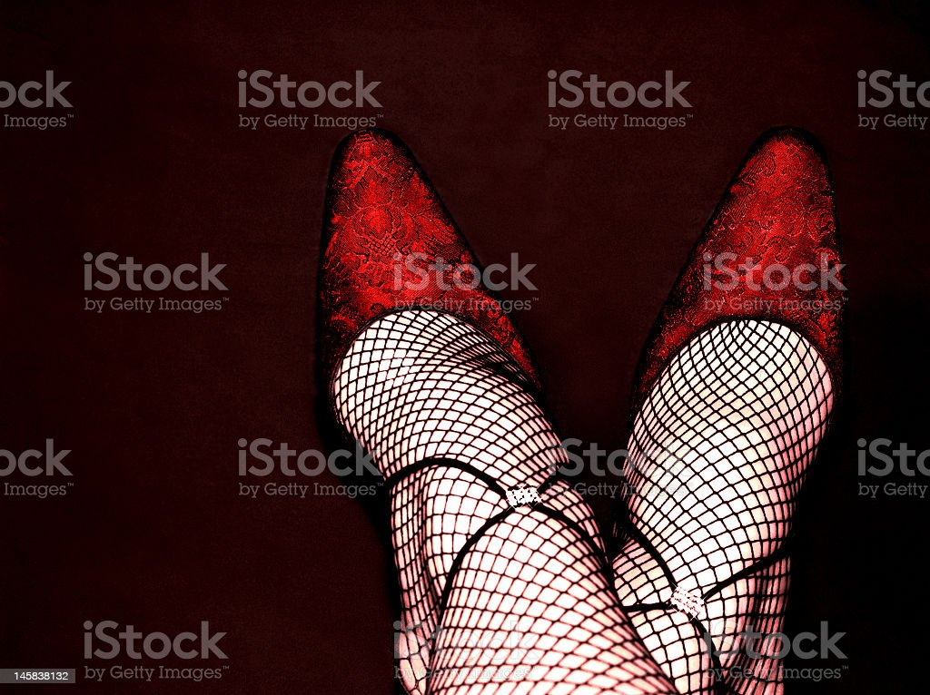 Woman's feet crossed, wearing red shoes and fishnet tights stock photo