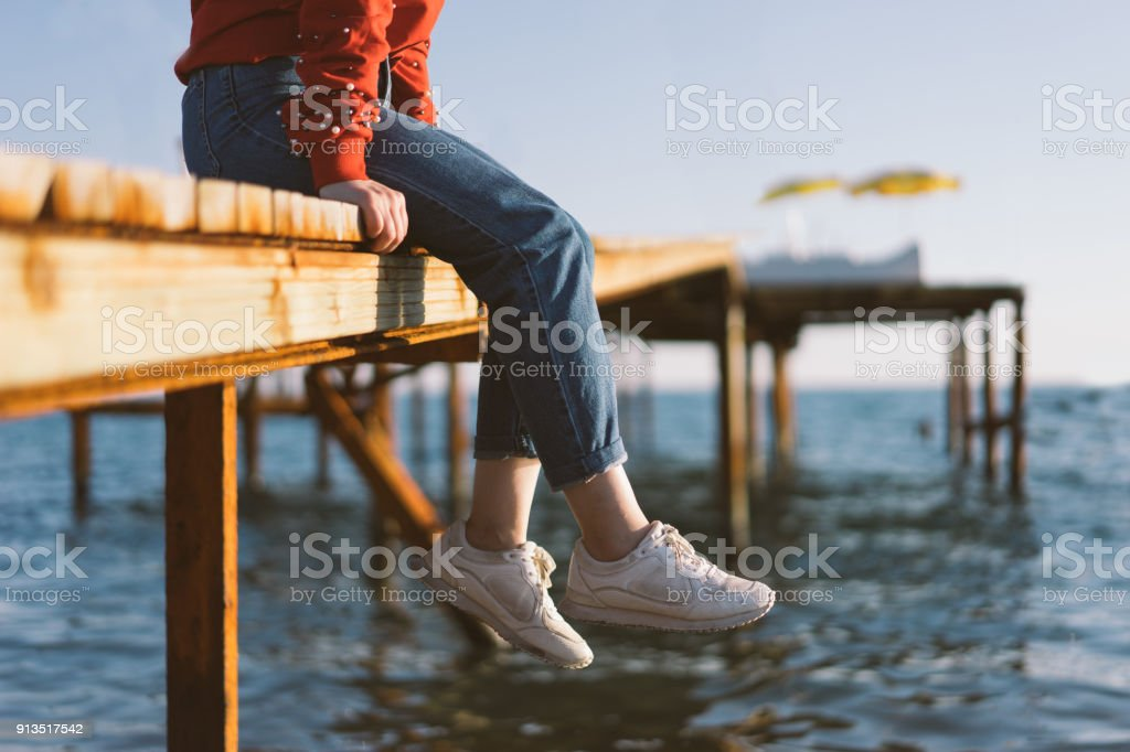 Woman's feet dangle from wooden wharf, above sea stock photo