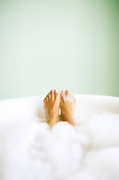 Woman's Feet Emerging in Bubble Bath  bathtub stock pictures, royalty-free photos & images