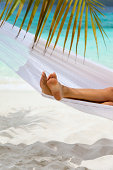 feet of an unrecognizable woman relaxing in a white hammock at a beach in the Caribbean